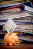 Hucha con la nota euro contra la pila de carpetas Imagenes de archivo