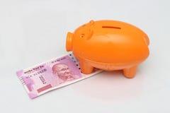 Hucha con las nuevas 2000 notas de la rupia en el fondo blanco Fotografía de archivo libre de regalías