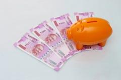 Hucha con las nuevas 2000 notas de la rupia en el fondo blanco Imágenes de archivo libres de regalías