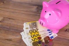 Hucha en billetes de banco euro con las monedas en la tabla Foto de archivo
