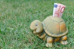 Hucha feliz de la tortuga con el billete de banco del euro diez Imágenes de archivo libres de regalías