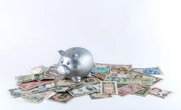 Hucha metálica de plata en la pila de billetes de banco Foto de archivo libre de regalías