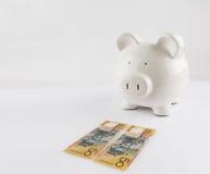 Hucha que se coloca cerca de dos billetes de dólar del australiano 50 Foto de archivo libre de regalías