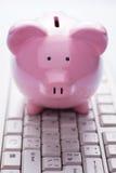 Hucha rosada en un teclado de ordenador Fotos de archivo