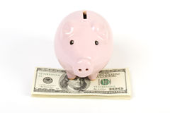 Hucha rosada que se coloca en la pila de billetes de dólar del americano ciento del dinero imagenes de archivo