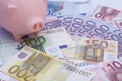 Hucha rosada rodeada por los billetes de banco euro Imagenes de archivo