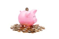 Hucha rosada y muchas monedas Imagen de archivo libre de regalías