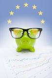 Hucha sobre carta del mercado de acción con la bandera europea en el fondo - parte de serie Fotografía de archivo libre de regalías