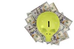 Hucha verde que se coloca en los billetes de dólar aislados sobre blanco Imagen de archivo