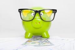 Hucha verde sobre carta del mercado de acción con 100 dólares de billete de banco Fotos de archivo libres de regalías