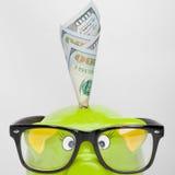 Hucha verde sobre carta del mercado de acción con 100 dólares de billete de banco - ratio 1 a 1 Imagen de archivo libre de regalías