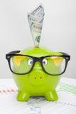 Hucha verde sobre carta del mercado de acción con 100 dólares de billete de banco Imagen de archivo