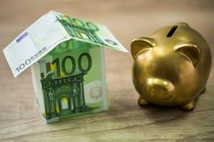Hucha y casa construidas de 100 billetes de banco euro Fotografía de archivo
