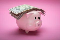Hucha y dinero en fondo en colores pastel rosado fotos de archivo libres de regalías