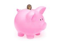 Hucha y moneda rosadas Imágenes de archivo libres de regalías