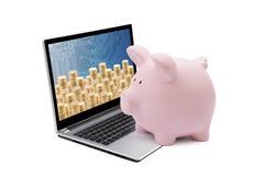 Hucha y ordenador portátil con las pilas de monedas de oro en el fondo blanco imagen de archivo libre de regalías