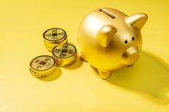 Hucha y pila de monedas de oro fotos de archivo