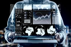 HUD and finance concept. Close up of hands holding laptop with digital business interface hologram on blurry night city background. HUD and finance concept royalty free stock images