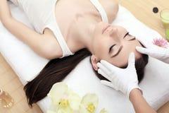 Hud och kroppomsorg Närbild av en ung kvinna som får Spa behandling på skönhetsalongen Spa vänder mot massage Ansikts- skönhetbeh arkivbild