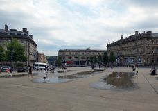 Families and children playing in the fountains in the pedestrian St. George`s Square in huddersfield yorkshire. Huddersfield, Yorkshire, England - Juiy 28 2018 royalty free stock images