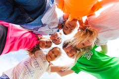 A huddle of school kids looking down at camera, stock photo