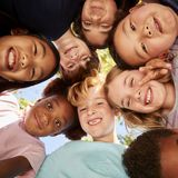 A huddle of school kids looking down at camera, close up royalty free stock image