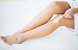 Hudomsorg och hälsa Hårborttagning Kvinnan med den rörande fjädern gör bar ben på säng royaltyfri bild