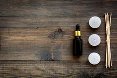 Hudomsorg och kopplar av Skönhetsmedel och aromatherapybegrepp Olja och stearinljus med kryddor som är kanelbruna på mörk träbakg Royaltyfri Bild
