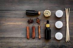 Hudomsorg och kopplar av Skönhetsmedel och aromatherapybegrepp Olja och stearinljus med kryddor som är kanelbruna på mörk träbakg Arkivfoto