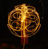 Hudozhniki juggling with two flaming poi's on fire. Prolonged exposure causes painting with light. Background. royalty free stock photography