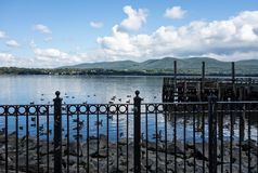 Hudson River Newburgh Waterfront. A scenic view of the Hudson River seen from the Newburgh waterfront.  A black iron fence, ducks and wooden dock are seen under Royalty Free Stock Images