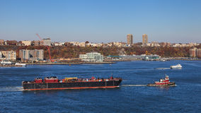 Hudson River Shipping. A tugboat tows a barge up the Hudson River.  The New Jersey waterfront can be seen in the background Royalty Free Stock Image