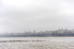 Hudson river in Winter with Misty New York Cityscape in Background. Royalty Free Stock Images