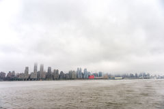 Hudson river in Winter with Misty New York Cityscape in Background. Royalty Free Stock Photo
