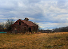 Hudson Valley old red barn and Catskill Mountains. Winter farmland and old red barn in Hudson Valley NY, with the sun setting and the Catskill Mountains in the royalty free stock image