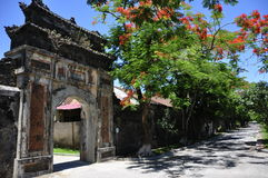 Hue Citadel Gate. Beautiful gate close to a tree with red flowers at the Hue Citadel, Vietnam Royalty Free Stock Photo