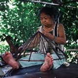 elderly woman making a traditional conical hat at her home royalty free stock photos