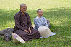 HUE, VIETNAM - CIRCA AUGUST 2015: Buddhist monks sit in the temples' yard on the   grass Stock Photo