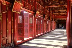 Hue / Vietnam, 17/11/2017: Corridor with red walls, open doors and ornamental golden decoration in a pavillion in the Citadel royalty free stock photo
