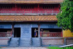 Hue / Vietnam, 17/11/2017: Couple standing inside a traditional house with ornamental tiled roof in the Citadel of Hue, Vietnam stock images