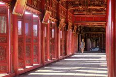 Hue / Vietnam, 17/11/2017: Woman passing through a red ornamental pavillion in the Citadel complex in Hue, Vietnam stock image