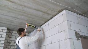 Hueco de relleno del constructor entre la pared y el techo con espuma del montaje almacen de video