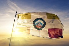 Huehuetenango Department of Guatemala flag textile cloth fabric waving on the top sunrise mist fog. Beautiful stock photo