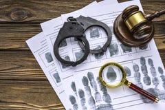 Huella dactilar del delincuente, esposas, martillo del juez fotos de archivo