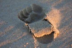 Huella en la arena de la playa en la puesta del sol Foto de archivo