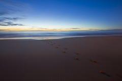 Huella en la arena en la noche, hora azul Imagenes de archivo
