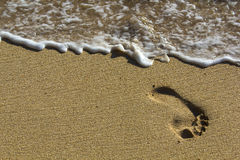 Huella en la playa con las ondas Fotos de archivo