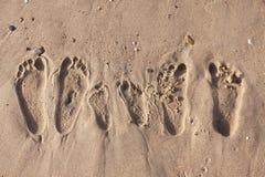 Huellas de la familia en la playa de la arena fotos de archivo libres de regalías