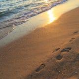 Huellas de un hombre y de un niño adultos en la arena en la playa en la puesta del sol Fotos de archivo