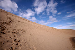 Huellas en desierto bajo el cielo nublado azul fotografía de archivo libre de regalías